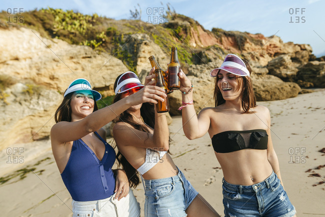 Three young women toasting with beer on the beach