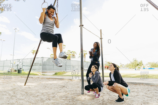 Smiling friends encouraging woman exercising on gymnastic rings at park against sky