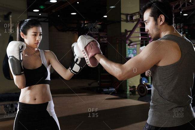 The coach guided the young woman to boxing