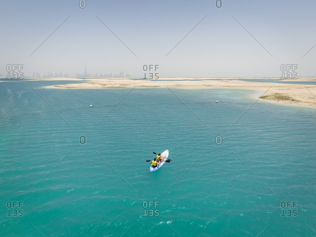Aerial view of a couple kayaking in the middle of The world islands in Dubai, United Arab Emirates.