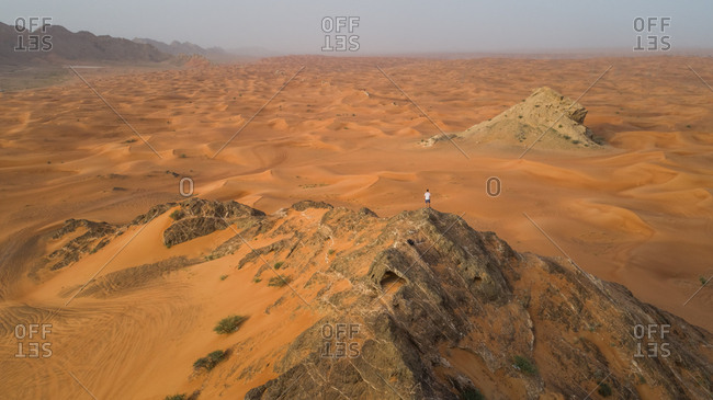 Aerial view of a man on the top of a rocky mountain in the Camel Rock Desert Safari in UAE.