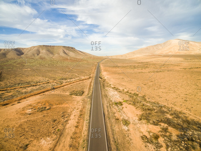 Aerial view of an empty road in dry land of Fuerteventura, Canary Islands.
