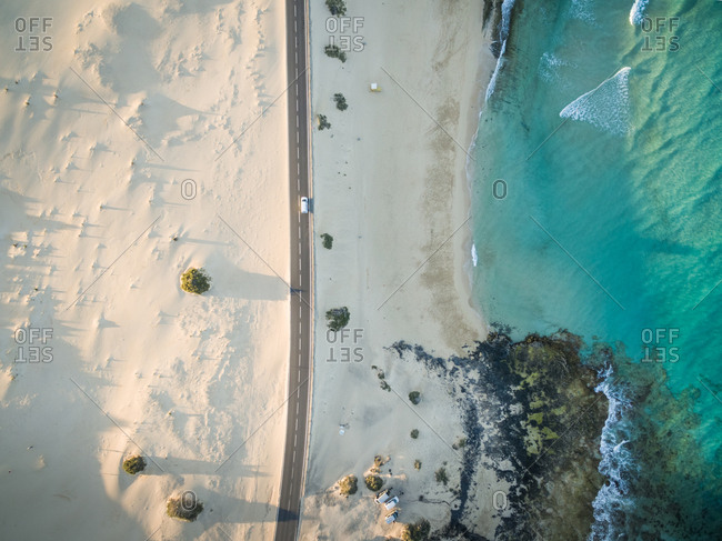 Aerial view of a car driving on the road in Corralejo Dunes Natural Park in Fuerteventura, Canary Islands.
