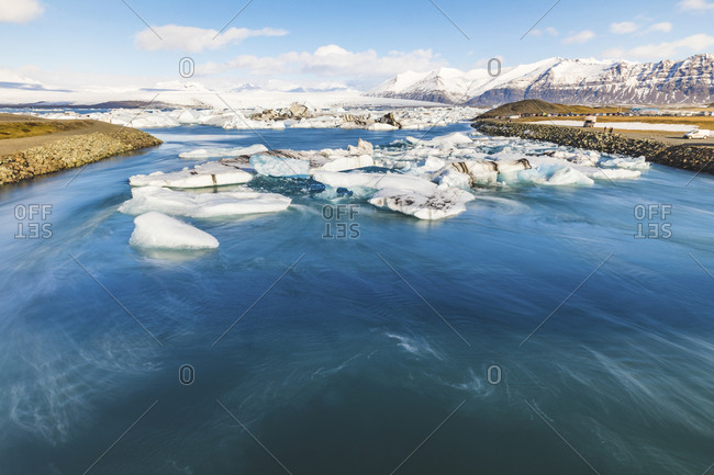 Hof, Iceland - March 15, 2017: Jokulsarlon lagoon with icebergs and mountains