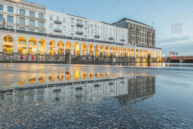 Hamburg, Germany - January 28, 2018: Kleine Alster with Alsterarkaden in the evening- mirrored in puddle