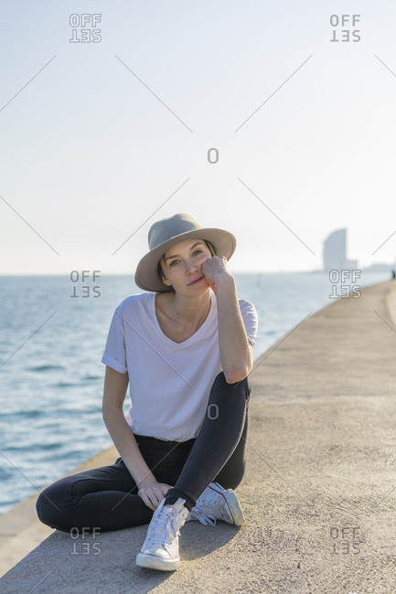 Spain- Barcelona- portrait of woman wearing hat sitting at waterfront promenade