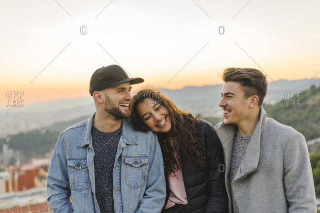 Portrait of three happy friends on a hill at sunset