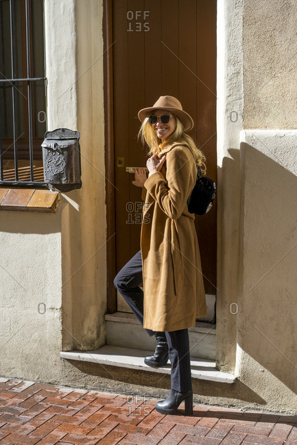 Portrait of fashionable young woman at house entrance