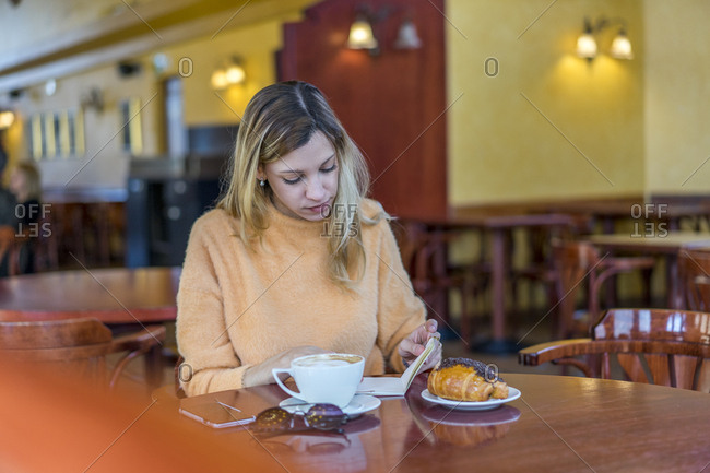 Young woman in a cafe with notebook- pastry and coffee