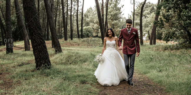 Happy bride and groom walking in forest
