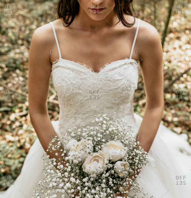 Close-up of bride holding bouquet of flowers in forest