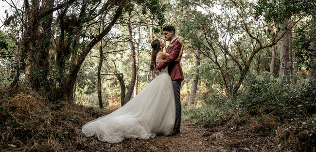 Bride and groom standing in forest embracing