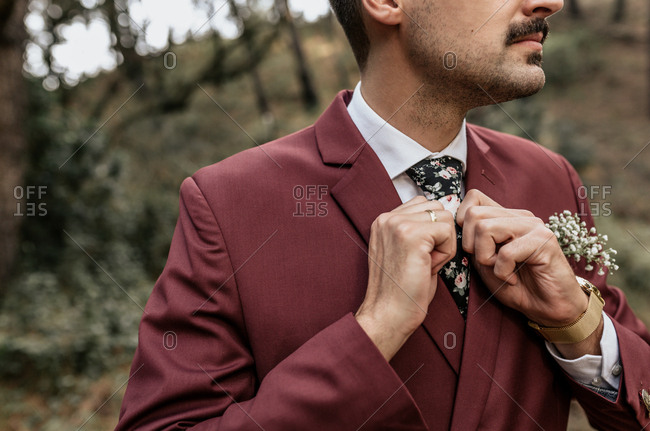 Close-up of man wearing a suit in forest adjusting his tie