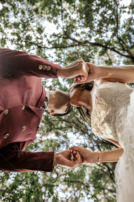 Bride and groom holding hands and kissing under a tree