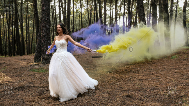 Woman wearing wedding dress in forest holding smoke torches