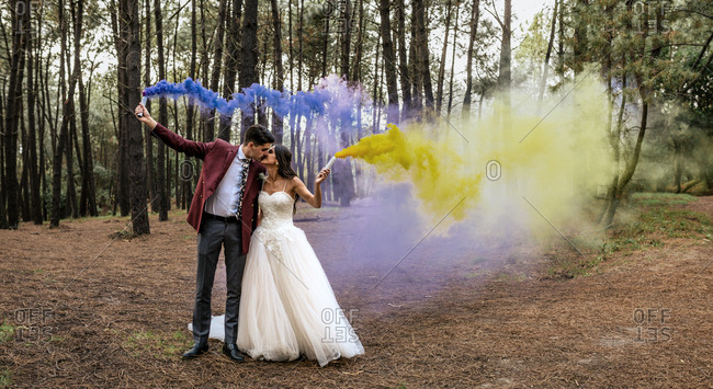 Bride and groom kissing in forest holding smoke torches
