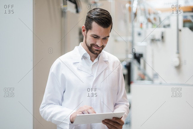 Man wearing lab coat in factory using tablet