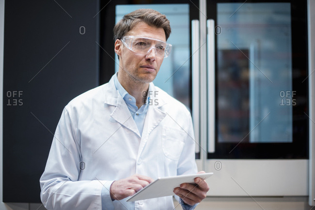 Portrait of man wearing lab coat and safety goggles holding tablet at machine
