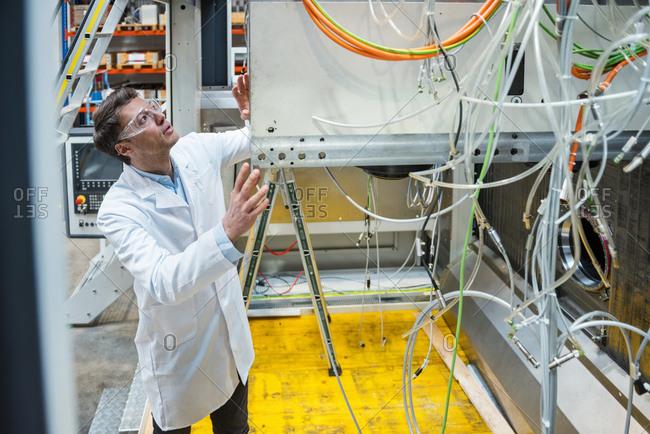 Man wearing lab coat and safety goggles examining at machine