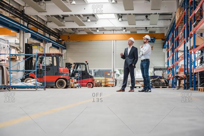 Two men wearing hard hats in factory shop floor