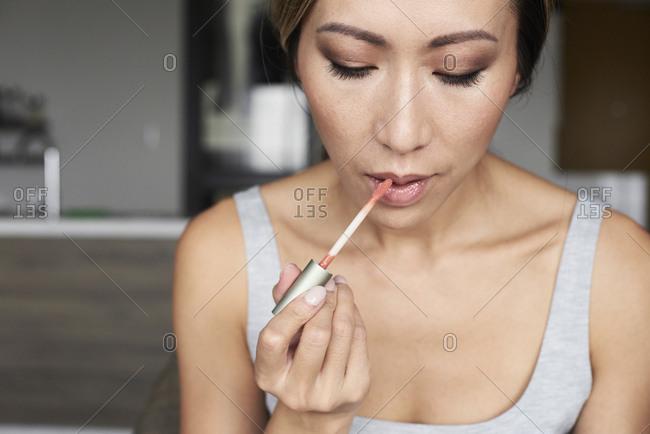 Woman at home using makeup applying lip gloss