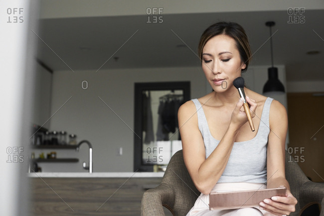 Woman at home using hand mirror applying makeup