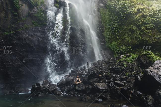 Indonesia- Bali- young woman practicing yoga at Sekumpul waterfall