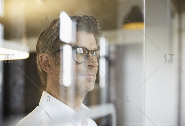 Mature businessman wearing glasses looking out of window