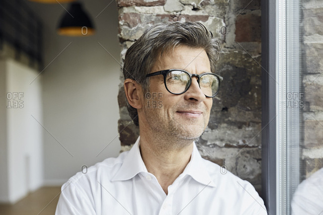 Portrait of smiling businessman wearing glasses looking out of window