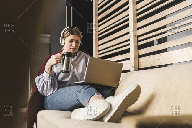 Young woman on couch with coffee and laptop
