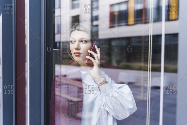 Young woman on cell phone behind windowpane