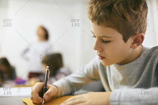 Schoolboy writing on desk in class
