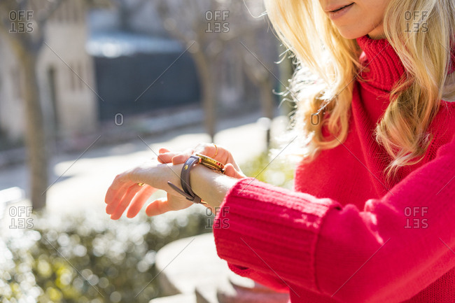 Close-up of woman using checking the time in a garden