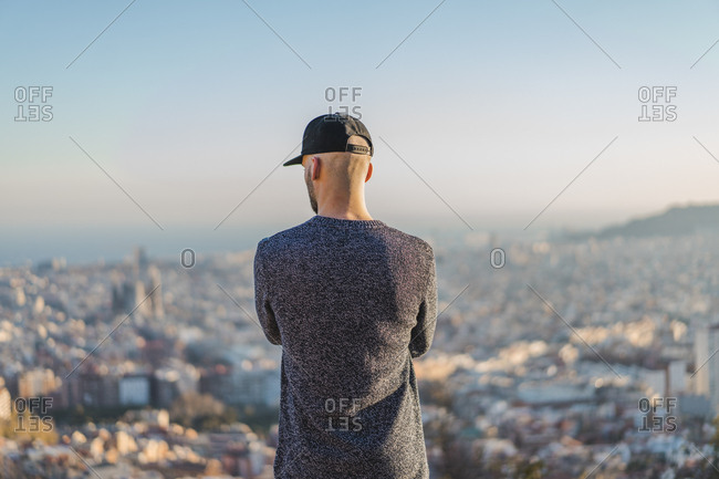 Spain- Barcelona- young man standing on a hill overlooking the city