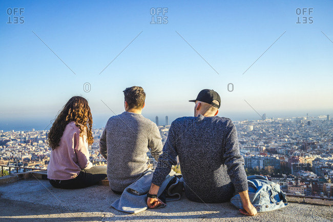 Spain- Barcelona- three friends sitting on a wall overlooking the city
