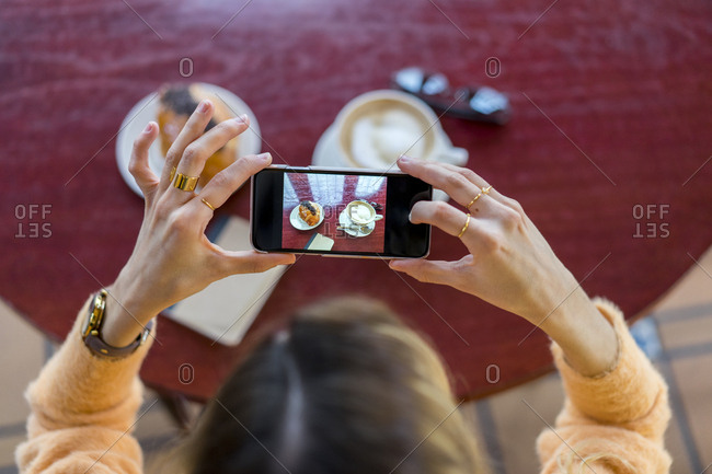 Overhead view of woman in a cafe taking cell phone picture