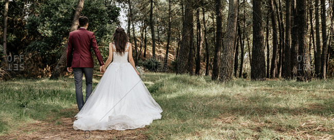 Back view of bride and groom walking in forest