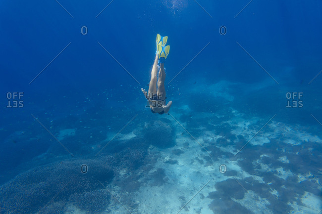 Woman with fins and snorkel diving under water
