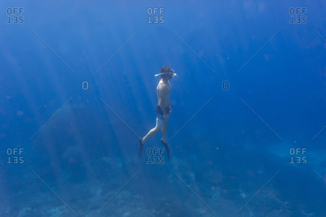 Man with fins and snorkel diving under water