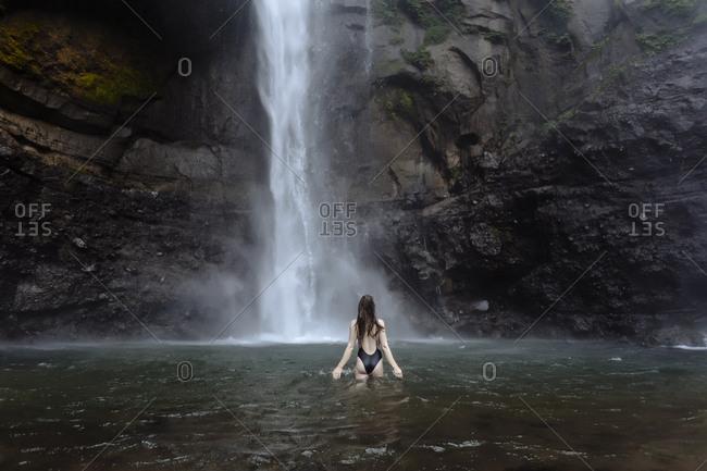 Indonesia- Bali- young woman bathing at Sekumpul waterfall