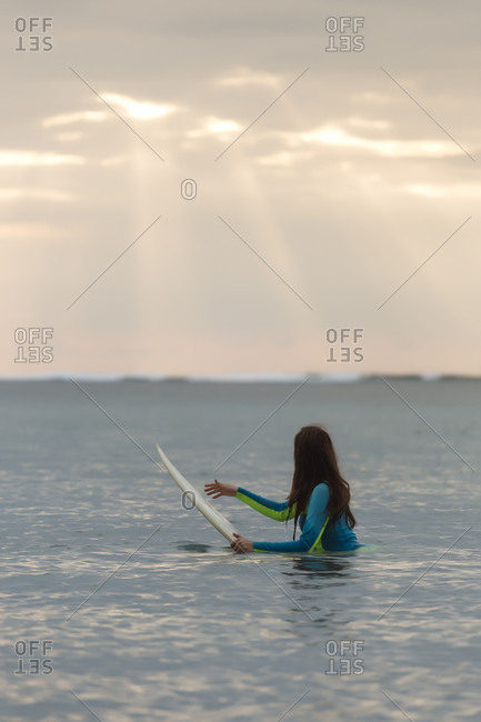 Indonesia- Bali- young woman with surf board in water