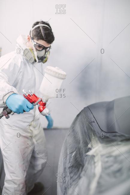 Auto painter painting a car