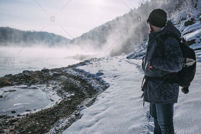 Russia- Amur Oblast- man standing in snow-covered landscape looking at  Bureya River