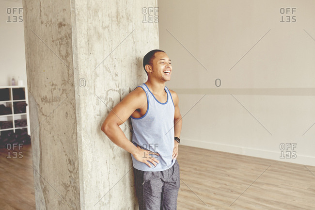 Happy tired young man standing with hand on hip in health club