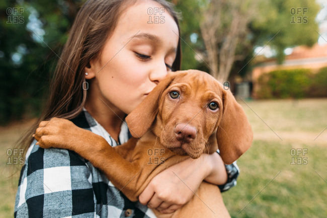 Girl giving her pet dog a kiss