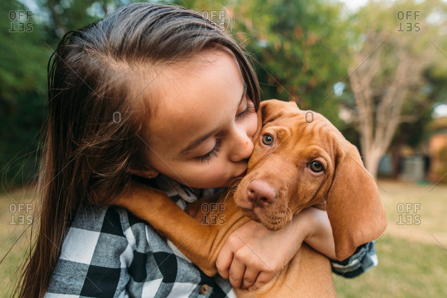 Girl kissing her pet dog