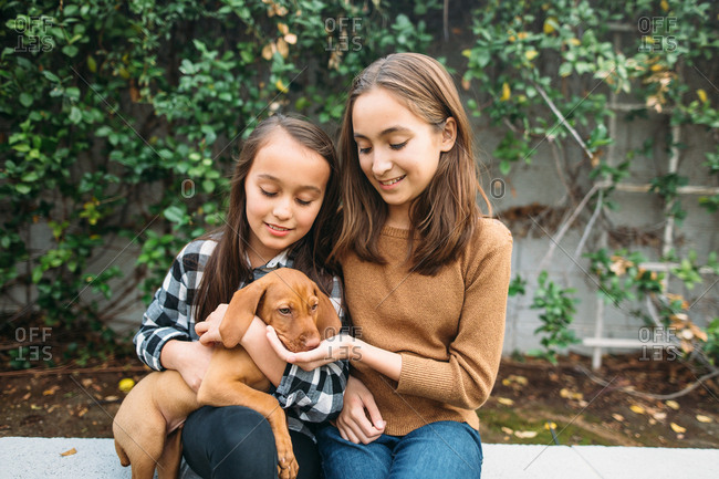 Two girls holding puppy