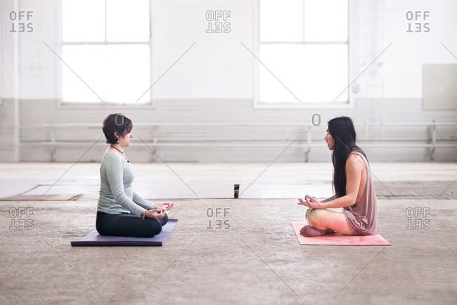 Two people sitting cross-legged towards each other practicing yoga in an empty factory