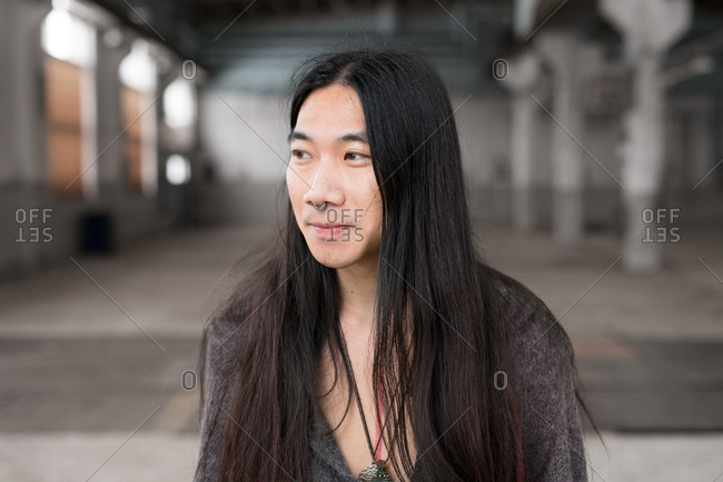 Portrait of a man with long dark hair and nose ring
