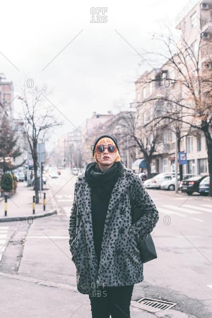 Woman wearing jacket and sunglasses standing on street corner